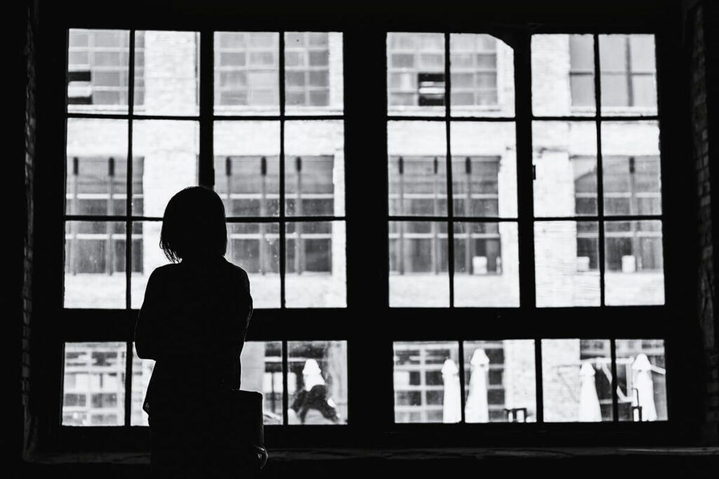 A silhouetted figure looks out from a window